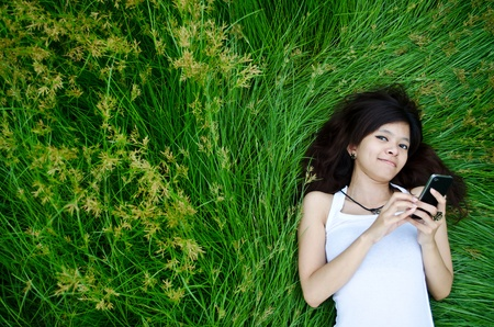 asian cute girl texting on meadow with happy face photo