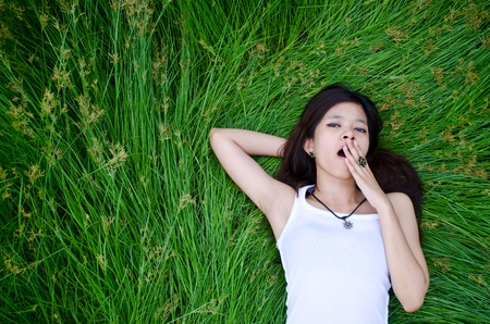 pregui�oso: asian girl lying on a meadow and yawn Banco de Imagens