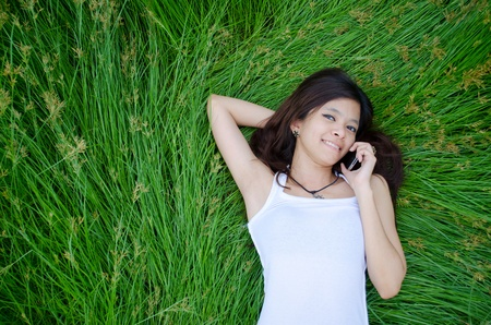 asian girl on phone lying on a meadow Stock Photo - 13408068