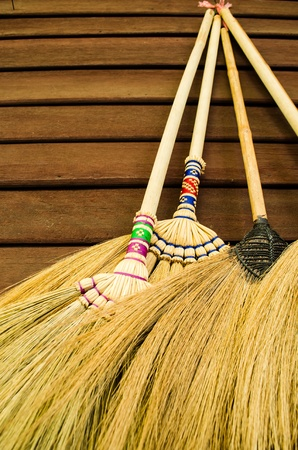 broom hanging on the wooden wall readdy for cleaning work Stock Photo