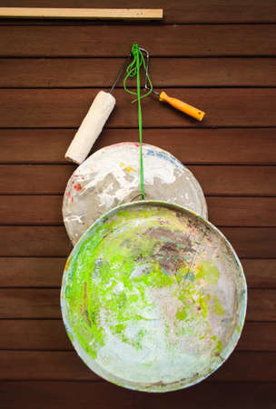 old palette made of jar's lid and a roller brush on wooden wall Stock Photo - 13842522