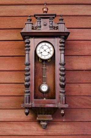 pendulum: antique wooden pendulum clock hanging on wooden wall Stock Photo