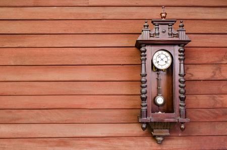 reloj de pendulo: antiguo reloj de péndulo de madera que cuelga en la pared de madera Foto de archivo