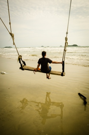lonely women siting on swing looking at sea