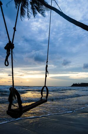 Silhouette of a swing at the beach on sunset