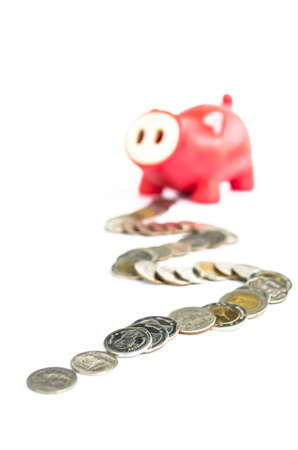 red piggy stand against pile of coin on white background