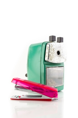 old green sharpener and pink stapleer on white background photo