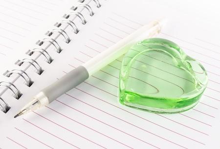 corazon cristal: verde coraz�n de cristal y una pluma en el cuaderno