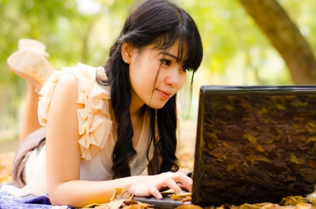 asian girl playing laptop in garden