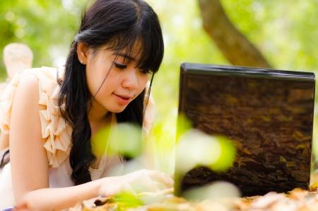 asian girl playing laptop in garden