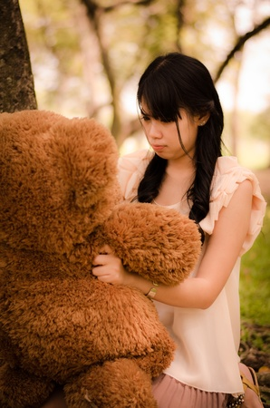 asian girl talking with the teddy bear in garden photo