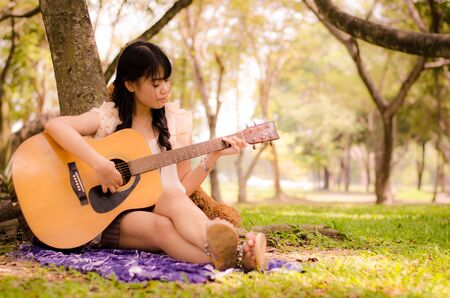 asian girl playing guitar under a tree in the garden Stock Photo - 17018763