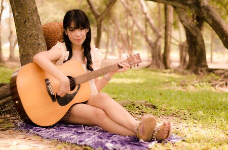 asian girl playing guitar under a tree in the garden Stock Photo - 17018764