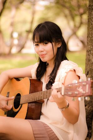 asian girl playing guitar under a tree in the garden Stock Photo - 17018691