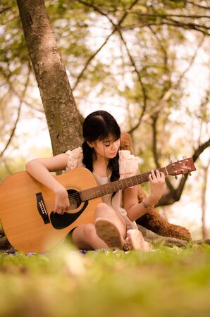 asian girl playing guitar under a tree in the garden Stock Photo