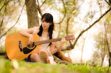 asian girl playing guitar under a tree in the garden Stock Photo - 17018692