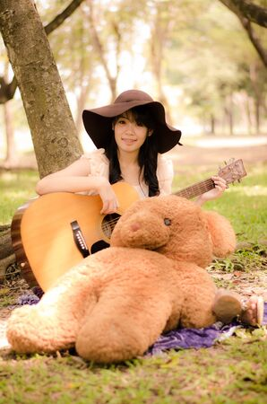 asian girl playing guitar under a tree in the garden Stock Photo - 17018693