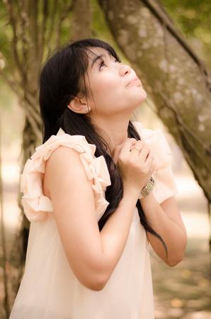 asian girl praying to the angel in garden