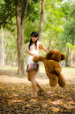 cute asian girl swinging a teddy bear around her self in the park photo