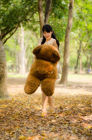 cute asian girl swinging a teddy bear around her self in the park