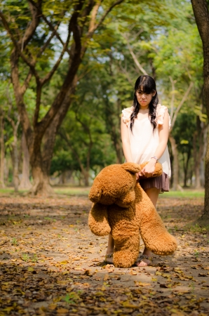 cute asian girl hanging a teddy bear in the park photo
