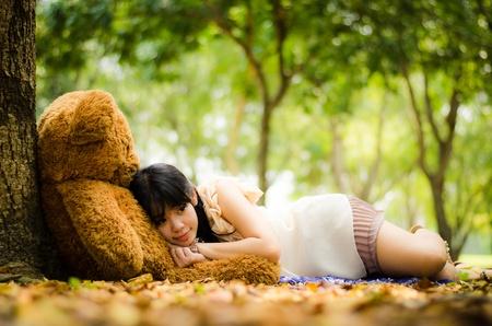 linda chica asiática descansando bajo un árbol con un oso de peluche