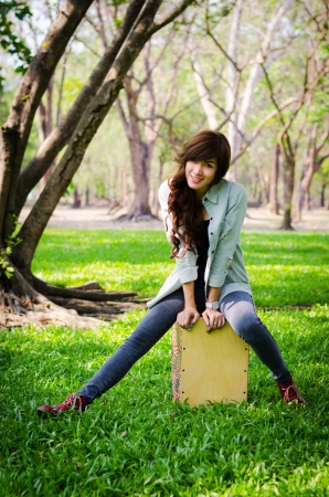 lady musician sitting on the cajon in public park photo