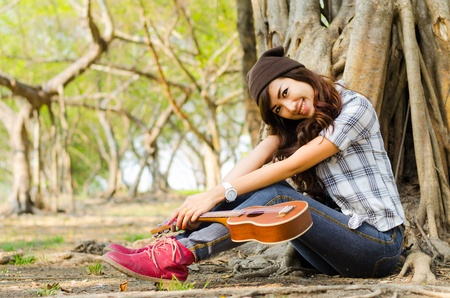 beautiful lady sitting under the tree with ukulele photo