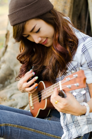 beautiful lady playing ukulele under  a tree Stock Photo