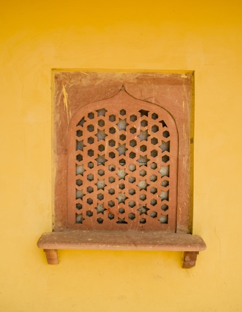 indian style window on yellow concret wall photo