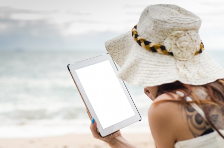 young woman using tablet on against beach background photo