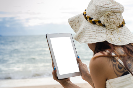 young woman using tablet on against beach background