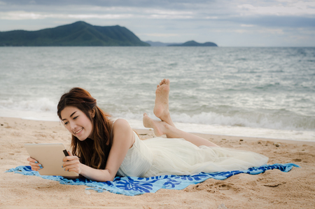 asian lady playing tablet on the beach