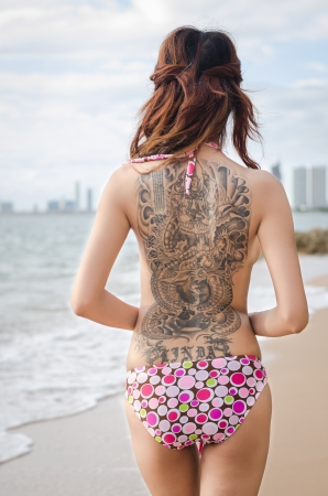 tattoos: asian girl showing her tattoo on the beach Stock Photo