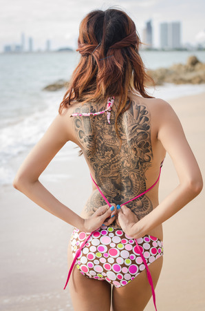 asian girl showing her tattoo on the beach Stock Photo