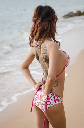 asian girl showing her tattoo on the beach photo