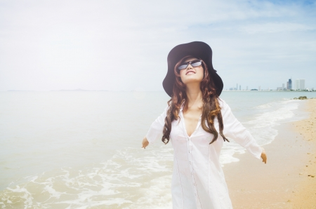 close up shot of a beautiful lady wearing white shirt agianst the beach Stock Photo
