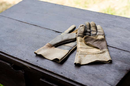 old leather gloves on wooden table photo