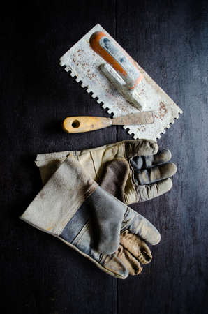 old leather gloves and rusty trowel on wooden table photo
