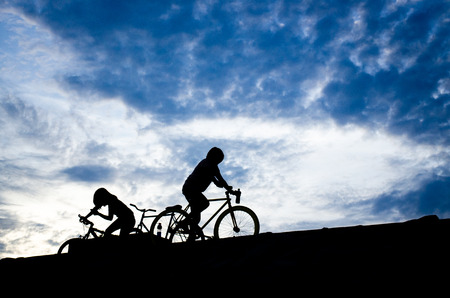 silhouette of tow biker against blue sky photo