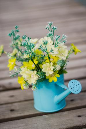plastic flower in blue pot on wood floor photo