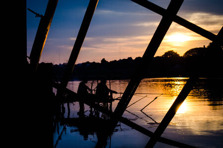 two fisherman silhouette against colour  sunset photo