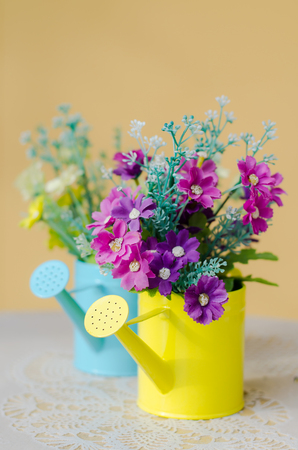plastic flower in blue pot on against yellow wall photo