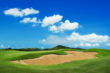 big sand trap in golf course against blue sky