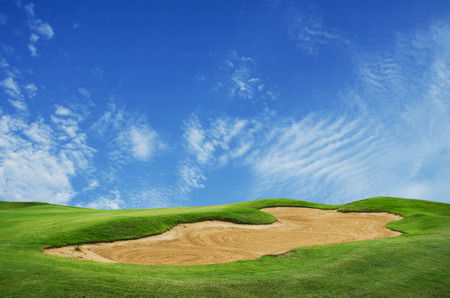 big sand trap in golf course against blue sky photo