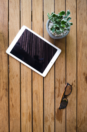 blank tablet on wooden desk with sun glasses