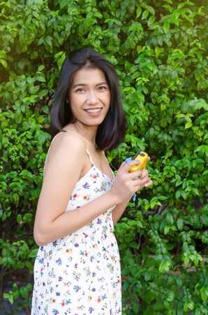 asian girl holding camera against green plant Stock Photo
