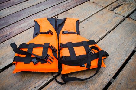orange life vest on wooden background Standard-Bild