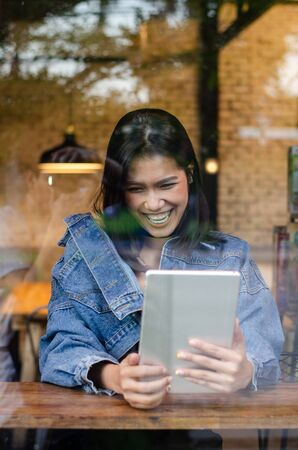 happy asian woman using tablet in cafe Stock Photo - 137593309
