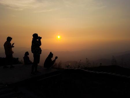 silhouette of couple taking photo of mountain peak against sunrise Stock Photo